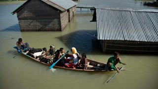 FILE - In this July 31, 2016, file photo, a flood-affected family with their goats travel on a boat in the Morigaon district, east of Gauhati, northeastern Assam state, India.