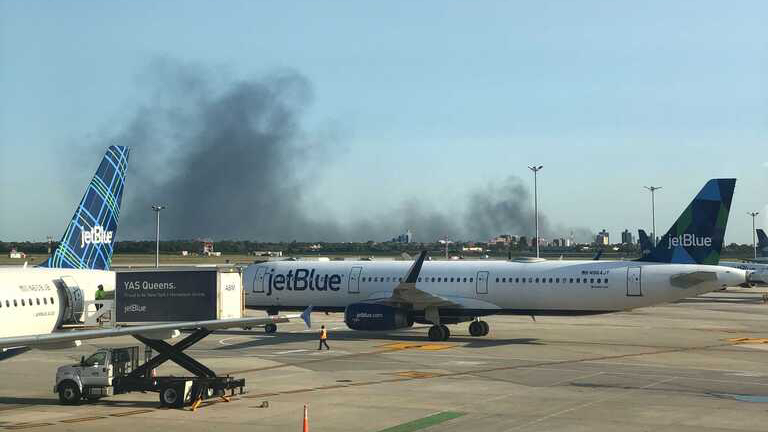 Black smoke filling the sky above Queens seen from JFK Airport.