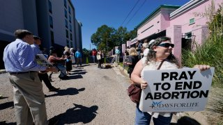 Anti-abortion activists gather for a small protest outside the Jackson Women's Health Organization clinic in Jackson, Miss.