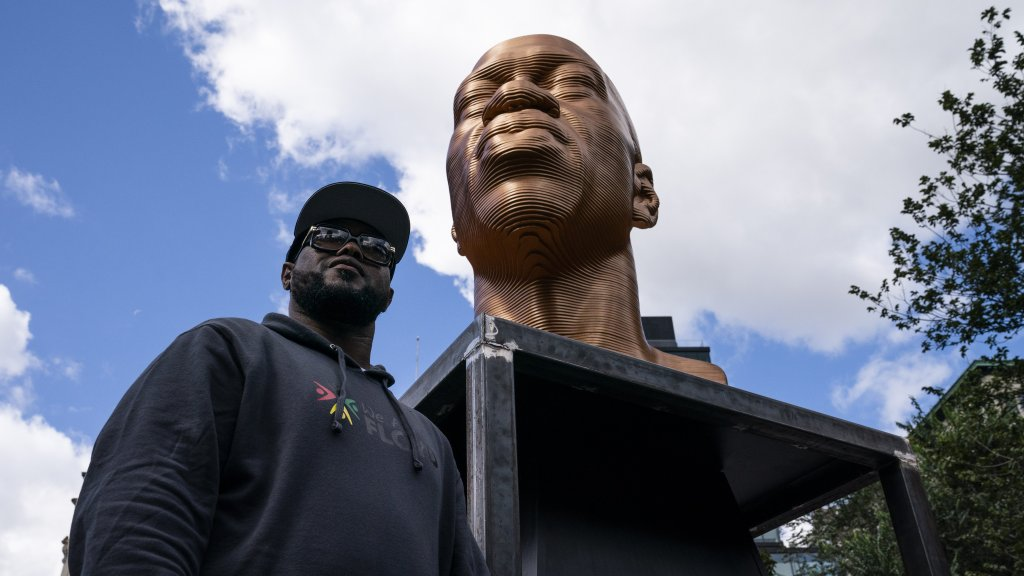Terrence Floyd stands beside a sculpture of his brother George Floyd