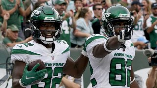 New York Jets wide receiver Jamison Crowder (82) celebrates his touchdown with running back Michael Carter (32) during the second half of an NFL football game against the Tennessee Titans