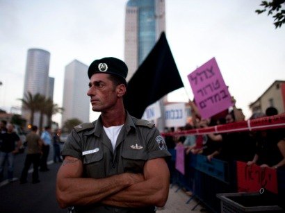 A border policeman looks on as Israeli left-wing protesters  demonstrate against Israel's deadly raid on an aid flotilla bound for  the blockaded Gaza Strip.