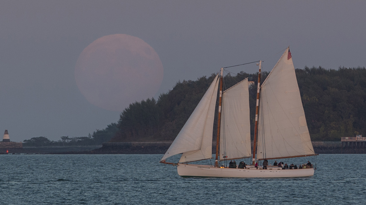 The supermoon that is also a blood moon rises over a sailboat in Boston Harbor on September 27, 2015. That supermoon coincided with a total lunar eclipse, a rare combination. A little over a year later, a new supermoon will be the closest the moon comes to earth since 1948. (Photo by Scott Eisen/Getty Images)