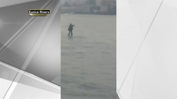 Man in Suit Paddleboards Across Hudson River