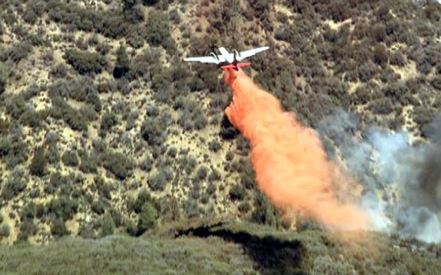 A firefighting aircraft drops retardant on a fire burning north of Los Angeles Monday June 3, 2013.