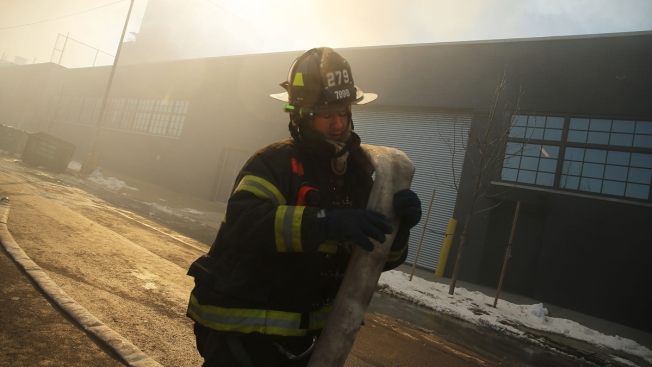 Firefighters Fight Smoldering Warehouse Fire for Second Day