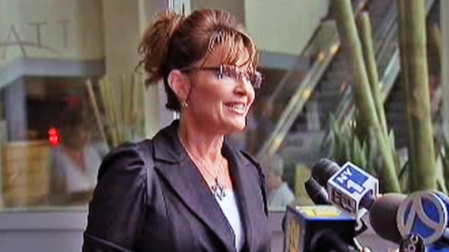 Sarah Palin pauses outside a Jersey City hotel to speak with members of the press ahead of her visit to Ellis Island and the Statue of Liberty.