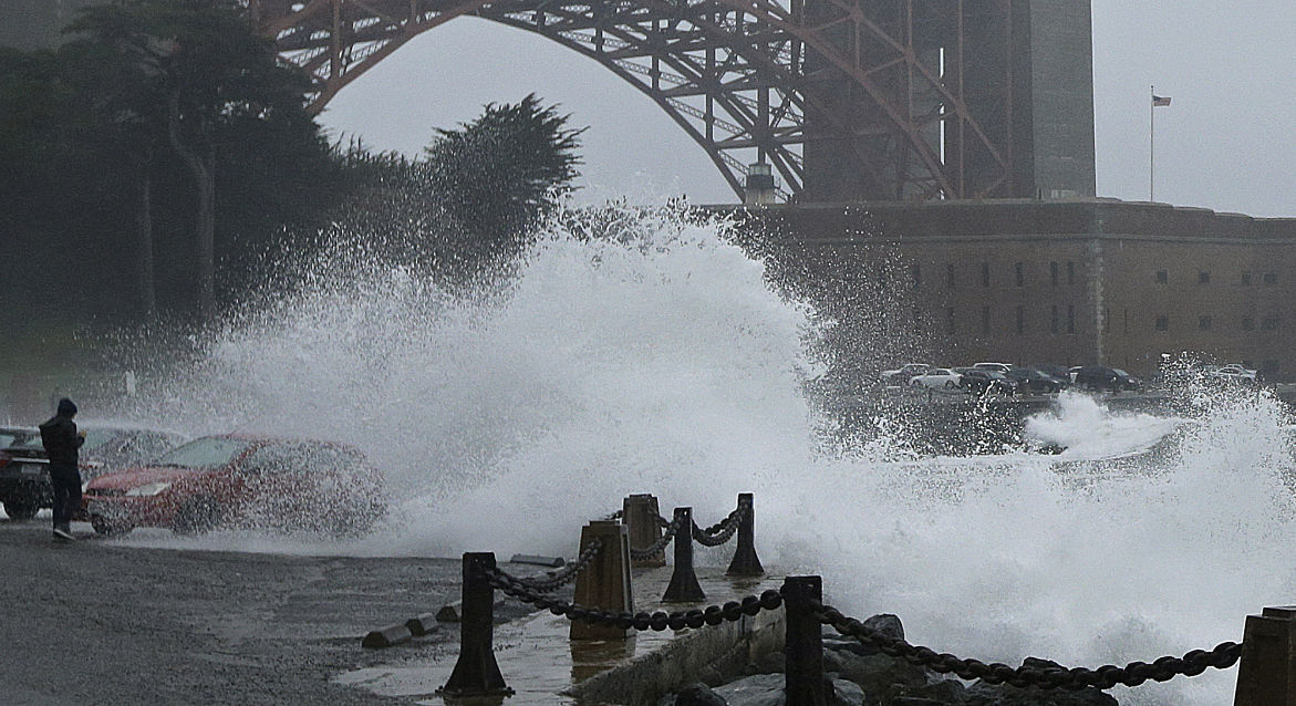 A man steps back from his car as a wave churned by the first significant winter storm of the year crashes at Fort Point near the Golden Gate Bridge, Friday, Oct. 14, 2016, in San Francisco.