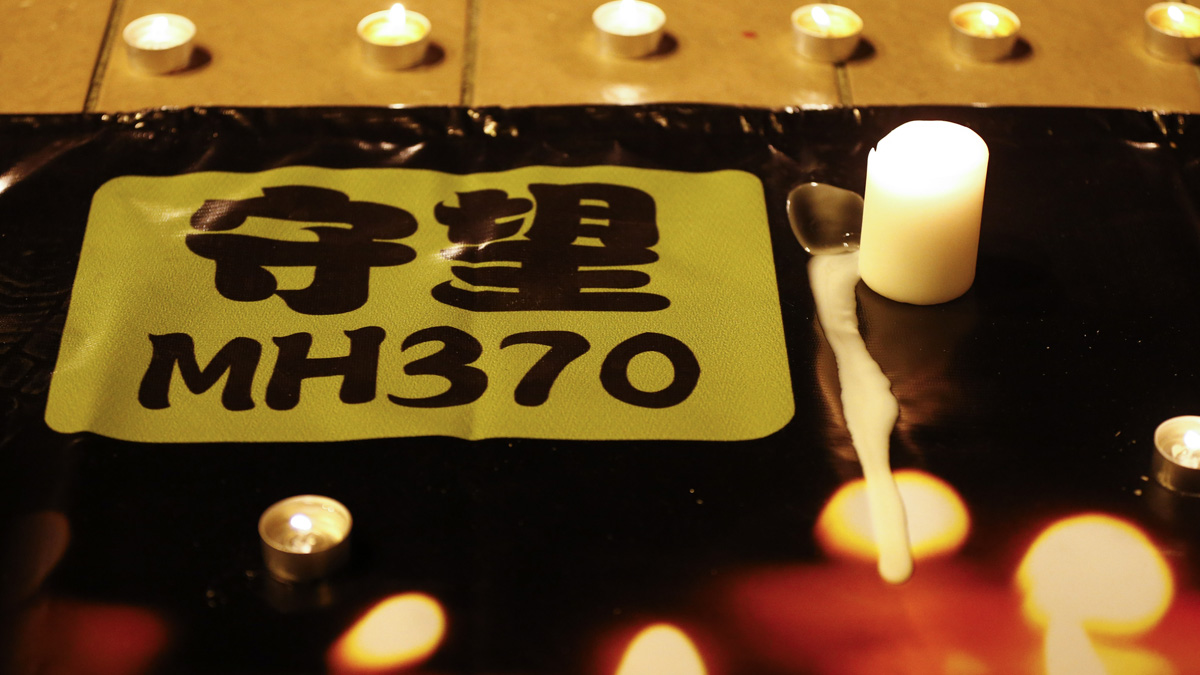 A banner is displayed during a candlelight vigil for passengers onboard the missing Malaysia Airlines Flight MH370, in Kuala Lumpur, Malaysia, Monday, April 7, 2014.