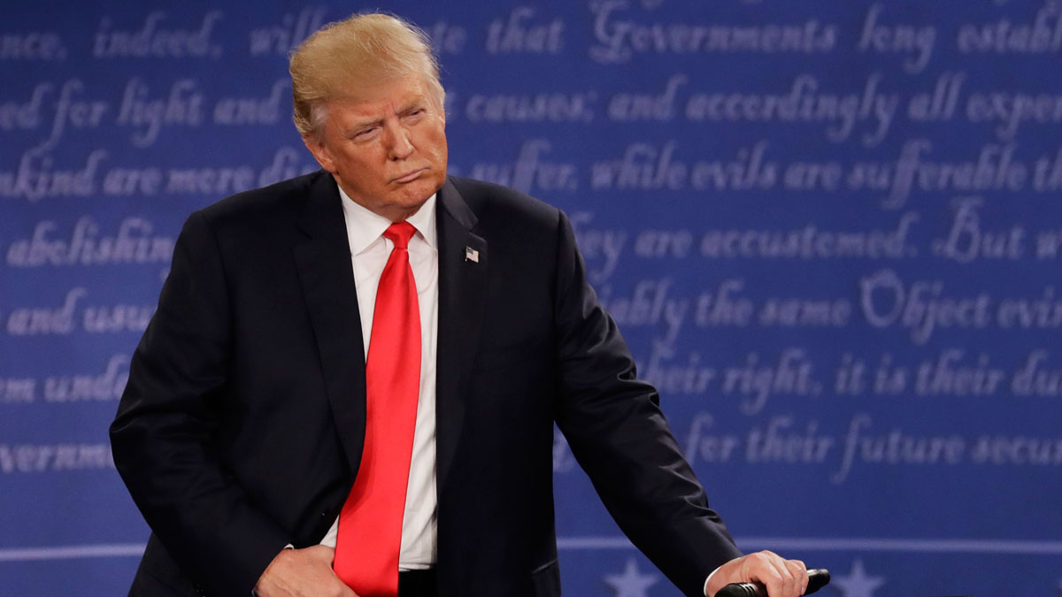 Republican presidential nominee Donald Trump listens to Democratic presidential nominee Hillary Clinton during the second presidential debate at Washington University in St. Louis, Sunday, Oct. 9, 2016. Two Trump donors are now asking for a refund over their disagreements with the GOP candidate.