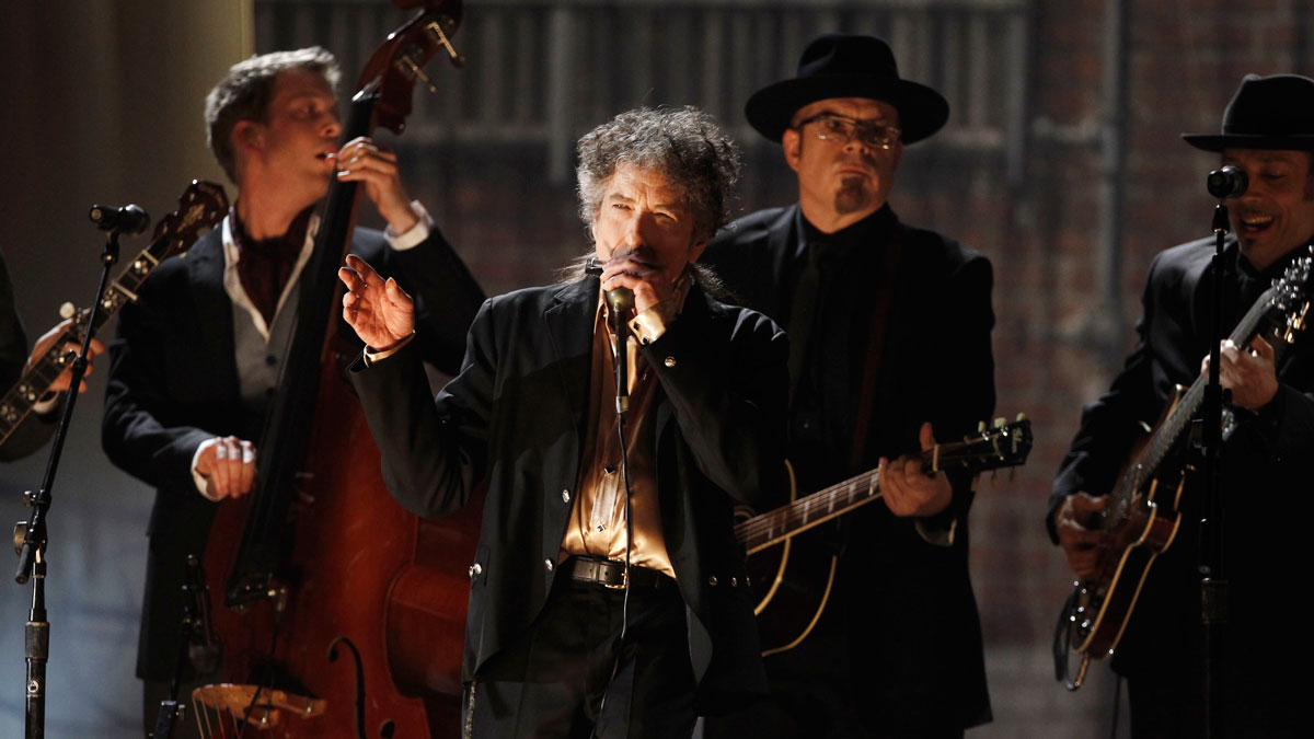 In this Feb. 13, 2011, file photo, Bob Dylan, center, performs at the 53rd annual Grammy Awards in Los Angeles.