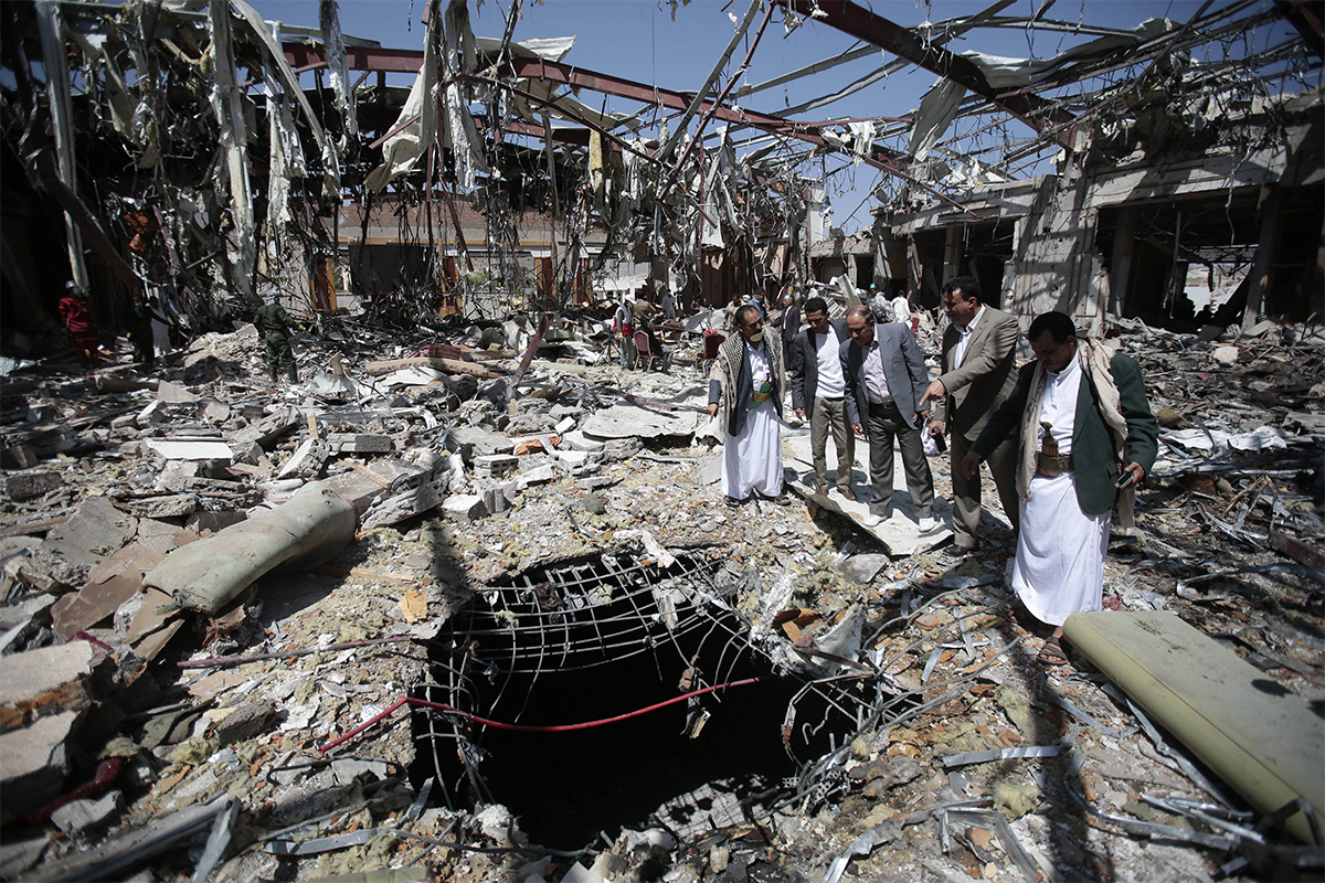 Members of the Higher Council for Civilian Community Organization, inspect a destroyed funeral hall as they protest against a deadly Saudi-led airstrike on a funeral hall six days ago, in Sanaa, Yemen, on Oct. 13, 2016.