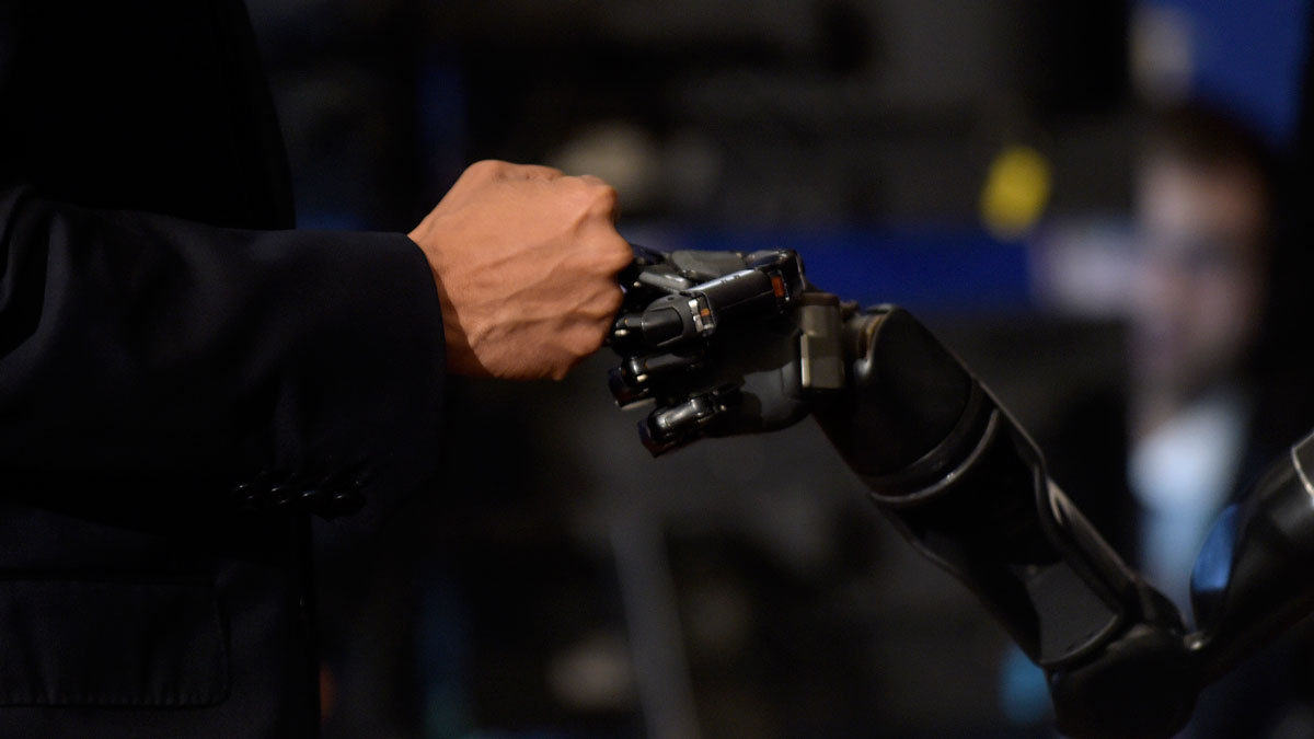 President Barack Obama does a fist bump with Nathan Copeland during a tour of innovation projects at the White House Frontiers Conference at University of Pittsburgh in Pittsburgh, Thursday, Oct. 13, 2016. Copeland demonstrates how he can control a robotic arm and feel when the robotic hand is touched.
