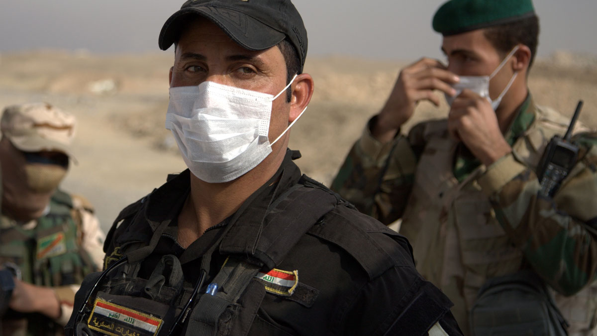 Iraqi troops wear masks as they guard a checkpoint near the village of Awsaja, Iraq, as smoke from fires lit by Islamic State militants at oil wells and a sulfur plant fills the air.