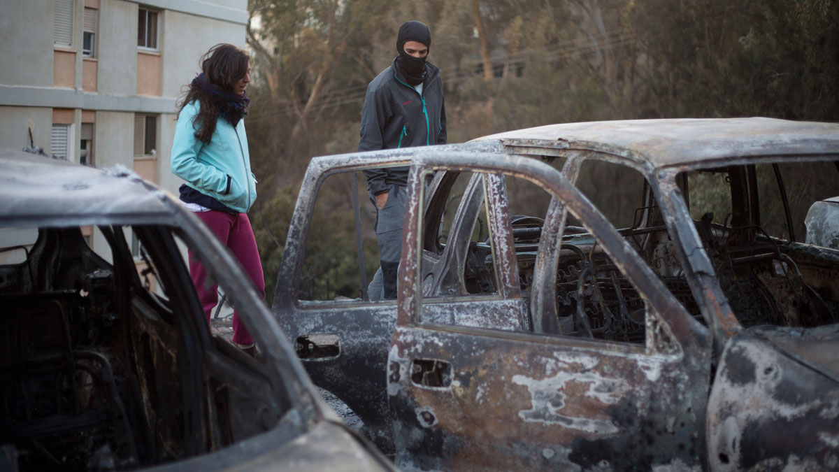 Residence stand near burned cars following a wildfires in Haifa, Israel, Friday, Nov. 25, 2016. Israeli firefighters on Friday reined in a blaze that had spread across the country's third-largest city of Haifa and forced tens of thousands of people to flee their homes, but continued to battle more than a dozen other fires around the country for the fourth day in a row.