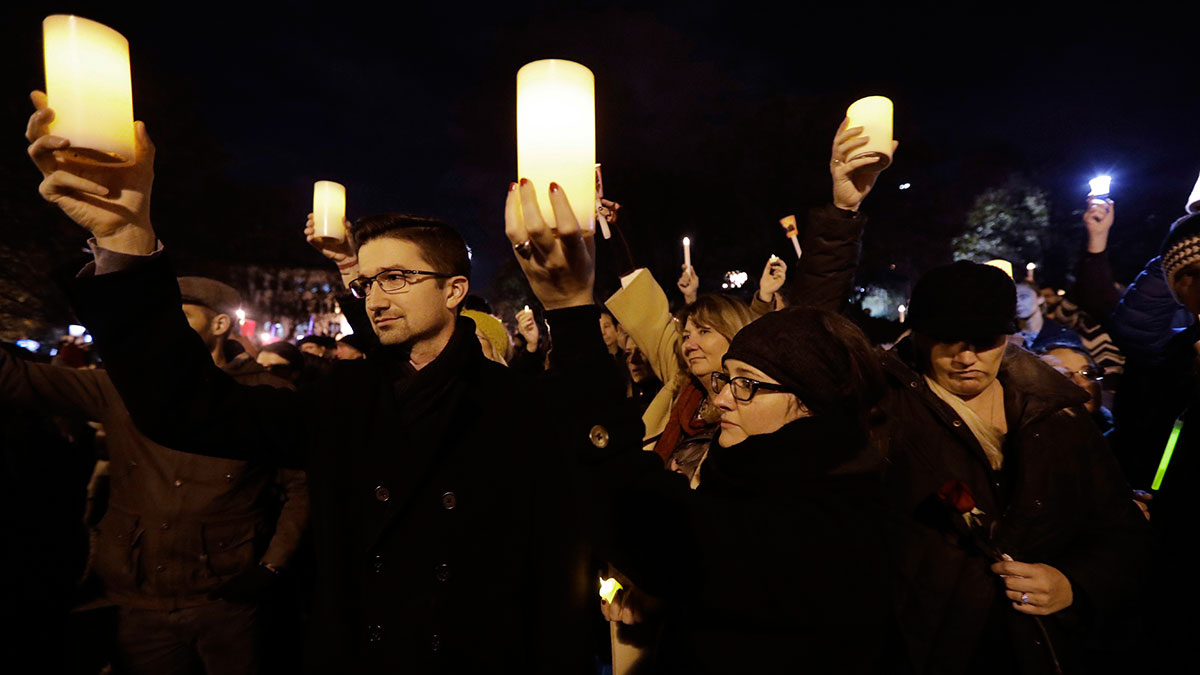 Relatives of Travis Hough, including cousin Jessica McDonald, second form right, and her partner Gero Zimmermann, at left, hold candles during a vigil in memory of victims of a warehouse fire at Lake Merritt on Monday, Dec. 5, 2016, in Oakland, California. Family members and friends are being notified as firefighters continue a painstaking search for victims of the Oakland warehouse fire.