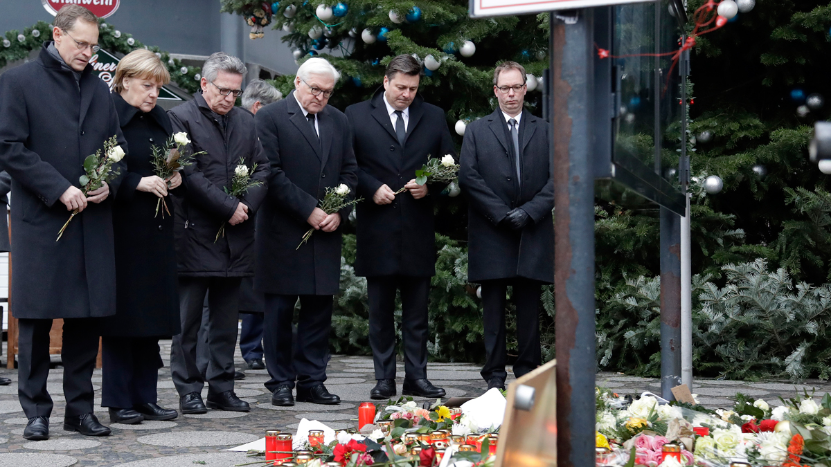 From left, the Mayor of Berlin Michael Mueller, German Chancellor Angela Merkel, German Interior Minister Thomas de Maiziere and German Foreign Minister Frank-Walter Steinmeier attend a flower ceremony at the Kaiser-Wilhelm Memorial Church in Berlin, Germany, Tuesday, Dec. 20, 2016 the day after a truck ran into a crowded Christmas market and killed several people.
