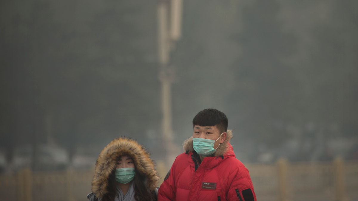 In this Saturday, Nov. 28, 2015, file photo, people wearing face masks walk across Tiananmen Square on a day with poor air quality in Beijing. The new WHO air quality monitor shows that 92 percent of people live in places with dirty air.