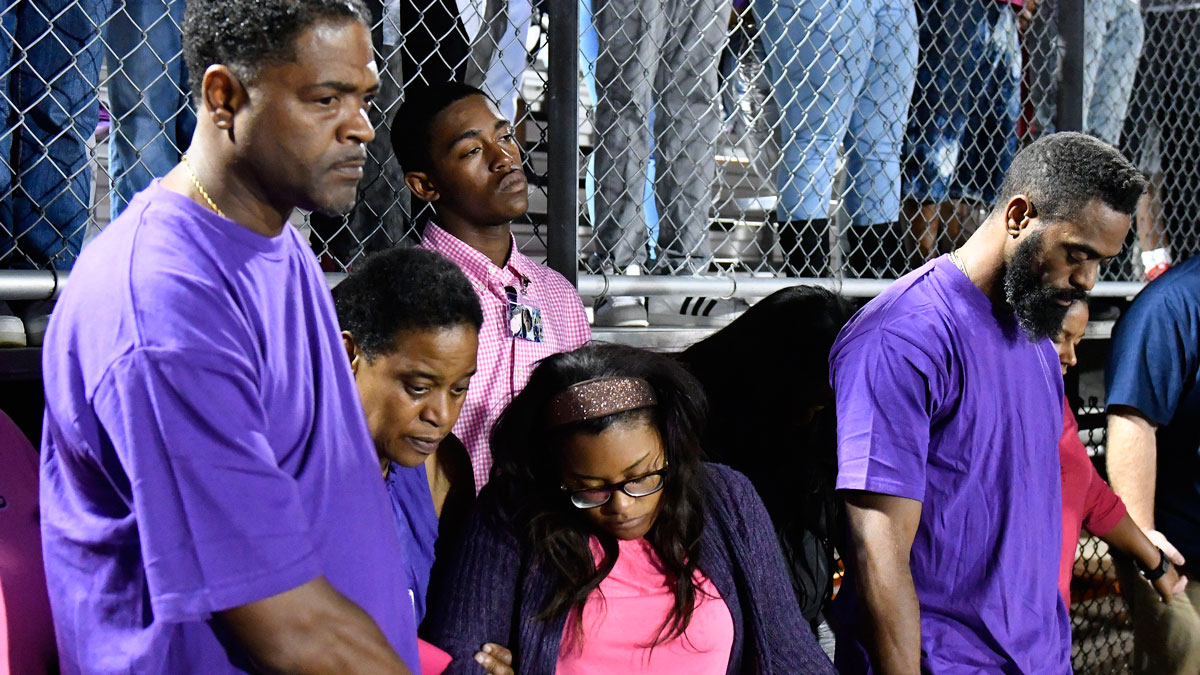 Tyson Gay, right, and Shoshana Boyd, second right, mother of Trinity Gay, hold hands during a moment of silence at a memorial service for their slain daughter at Lafayette High School on Oct. 17, 2016, in Lexington, Ky.