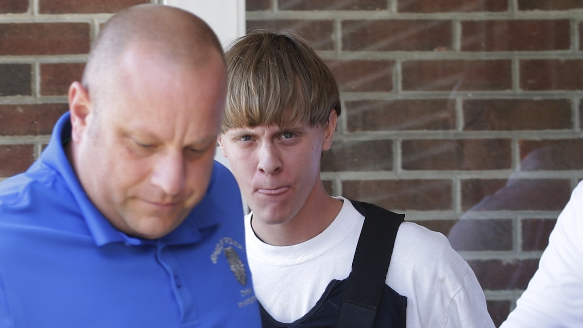 In this June 18, 2015, file photo, Charleston, S.C., shooting suspect Dylann Storm Roof, center, is escorted from the Sheby Police Department in Shelby, N.C. Joey Meek, a friend of Roof's, told an FBI agent that he did not know specifics about Dylann's plan to shoot the churchgoers during Bible study, but the FBI says that was a lie.