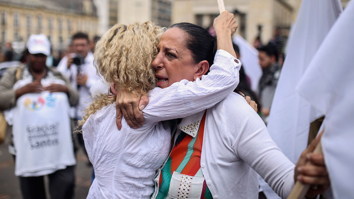 In this Thursday, Nov. 24, 2016, photo, women hug during a rally in support of the peace process with rebels of the Revolutionary Armed Forces of Colombia, FARC, a few blocks from the venue where Colombia's President Juan Manuel Santos and top FARC rebel leader Rodrigo Londono signed a revised peace pact, in Bogota, Colombia. An original accord ending the half century conflict was rejected by voters in a referendum last month.