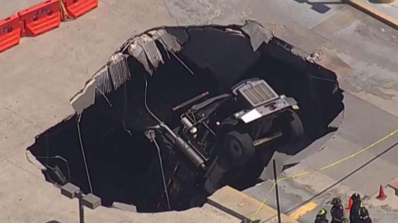 Dump Truck Crashes Through Top Floor of Parking Garage