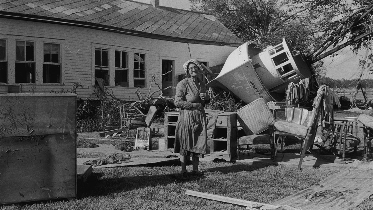 An elderly woman in an apron and bonnet stands in front of a house, which was hit by a boat when Hurricane Audrey struck Louisiana.