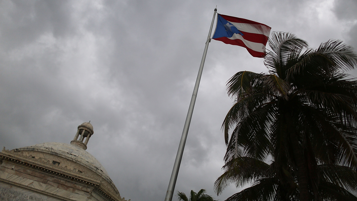 In this file photo, the Puerto Rican flag flies near the Capitol building.