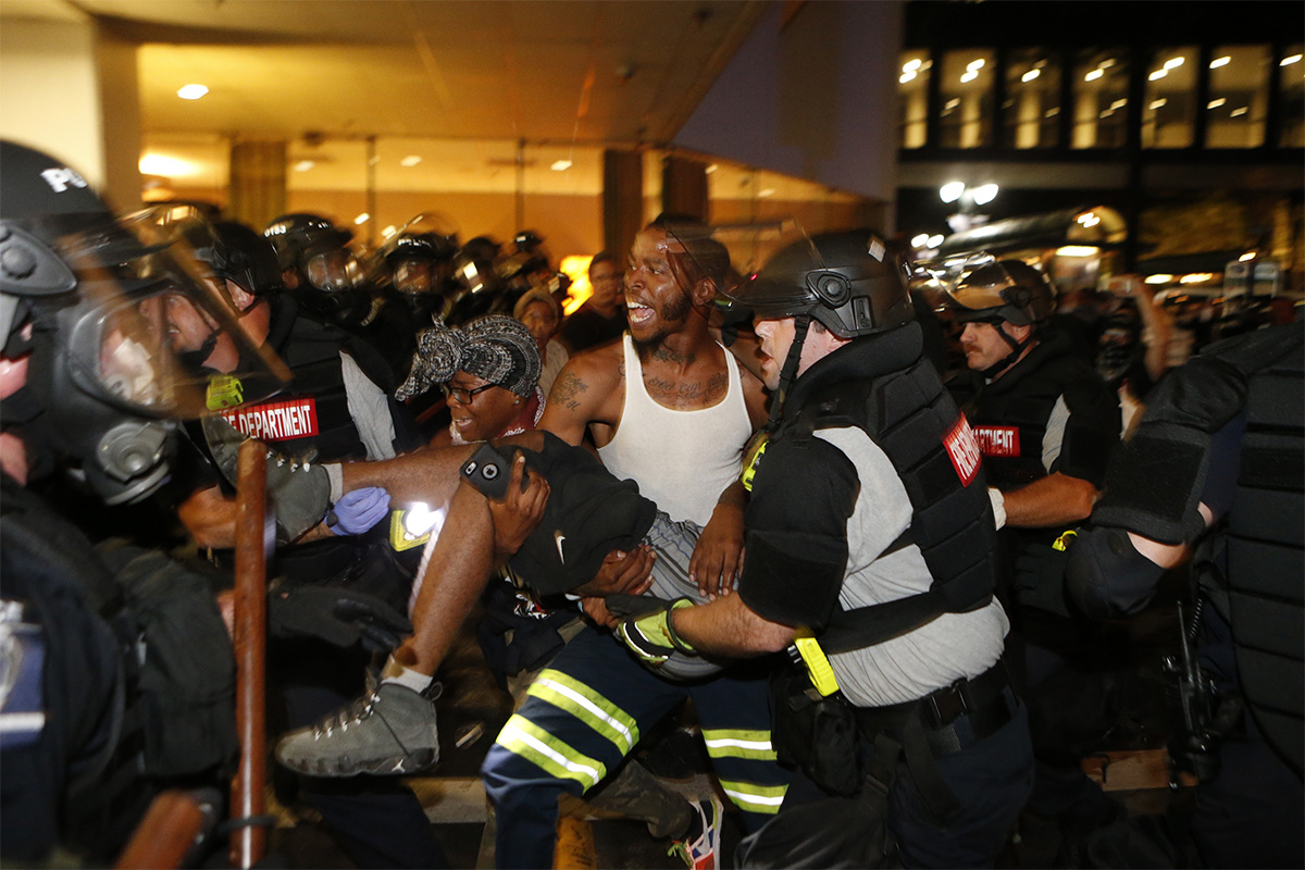 Police and protesters carry a seriously wounded protester into the parking area of a hotel during a march to protest the death of Keith Lamont Scott on Sept. 21, 2016, in Charlotte, North Carolina.