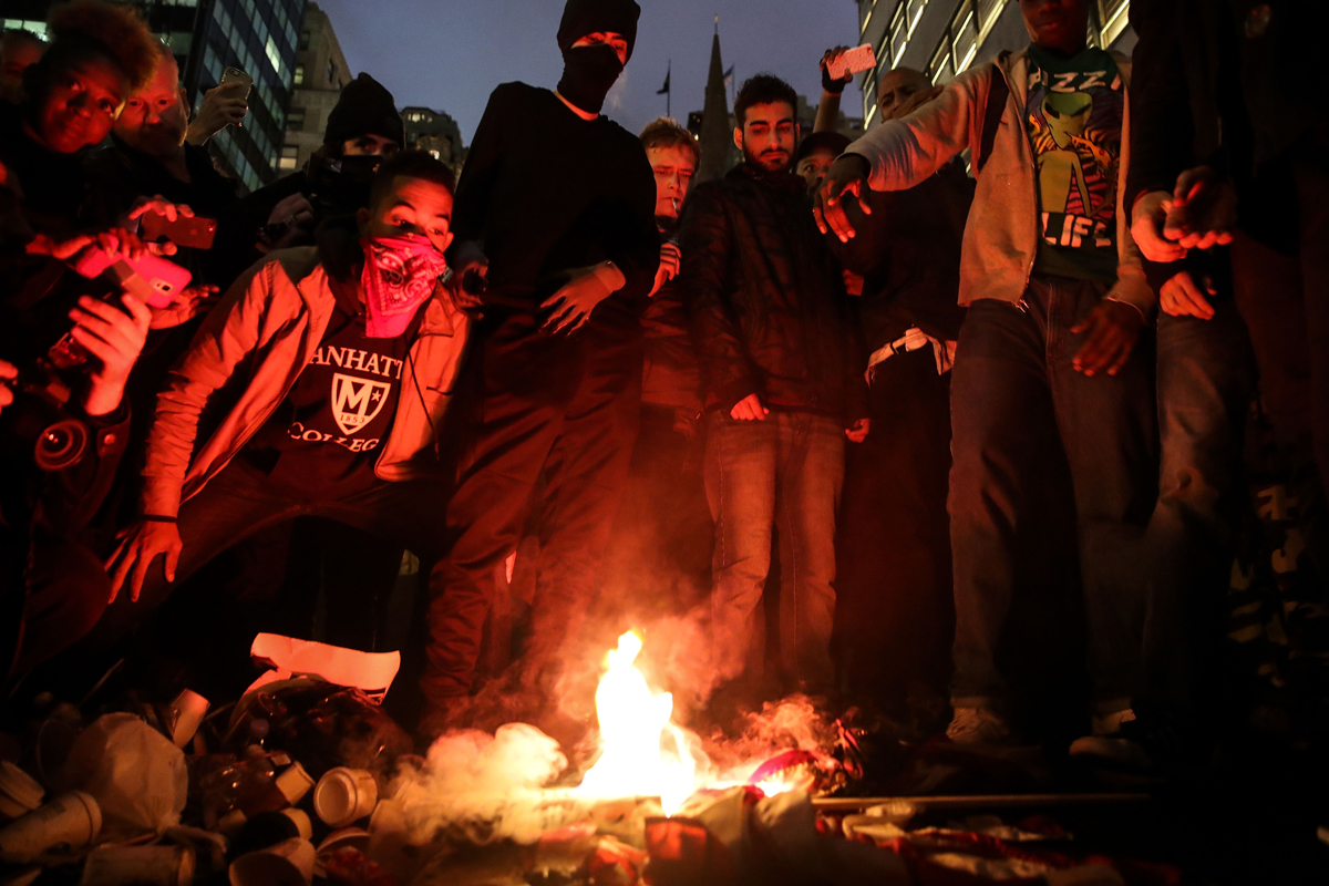 Protestors burn an American flag on Fifth Avenue outside of Trump Tower, Nov. 9, 2016, in New York City.