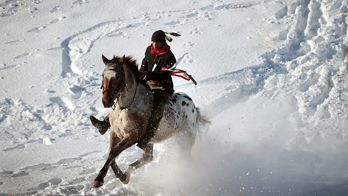 An Native American activist rides down from a ridge which overlooks Oceti Sakowin Camp on the edge of the Standing Rock Sioux Reservation on Dec. 4, 2016, outside Cannon Ball, North Dakota. Native Americans and activists from around the country have been gathering at the camp for several months trying to halt the construction of the Dakota Access Pipeline.