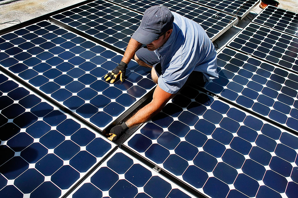 Damon Corkern, who works for ECS Solar Energy Systems, Inc, installs a solar panel system on the roof of a home on April 16, 2009 in Gainesville, Florida.