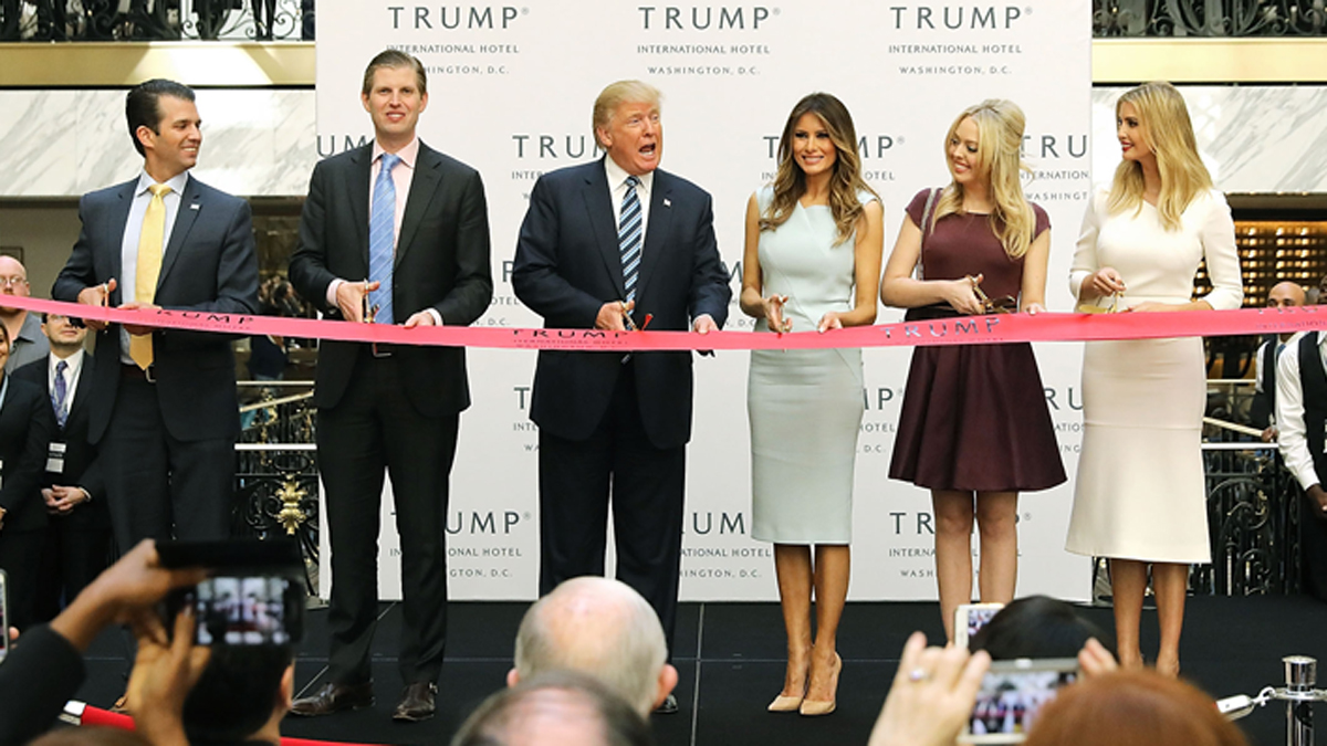 Republican presidential nominee Donald Trump (C) and his family (L-R) son Donald Trump Jr, son Eric Trummp, wife Melania Trump and daughters Tiffany Trump and Ivanka Trump cut the ribbon at the new Trump International Hotel October 26, 2016 in Washington, DC. The hotel, built inside the historic Old Post Office, has 263 luxry rooms, including the 6,300-square-foot 'Trump Townhouse' at $100,000 a night, with a five-night minimum. The Trump Organization was granted a 60-year lease to the historic building by the federal government before the billionaire New York real estate mogul announced his intent to run for president.