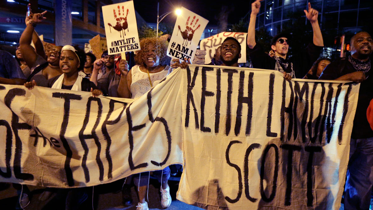 In this Friday, Sept. 23, 2016 file photo, protesters shout as they march in the streets of Charlotte, N.C., to protest the fatal police shooting of Keith Lamont Scott.