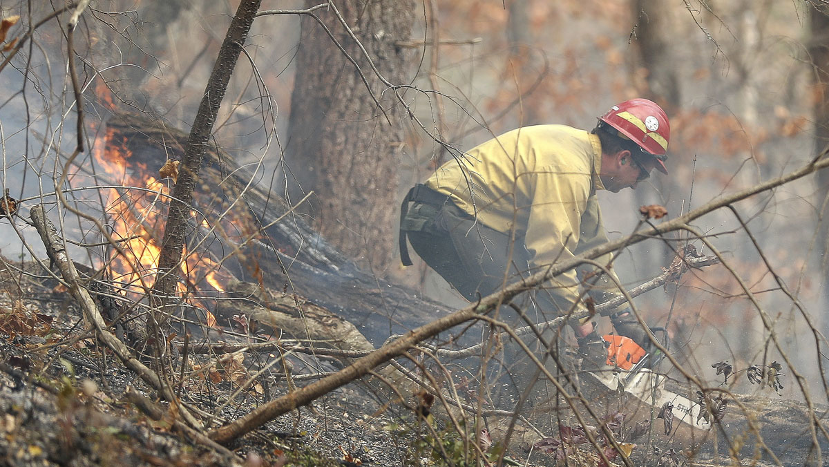 A firefighter battles a wildfire Tuesday, Nov. 15, 2016, in Clayton, Ga. On Tuesday, the Tennessee Valley Authority issued a burn ban on its public lands across Tennessee and in parts of Alabama, Georgia, Kentucky, Mississippi, North Carolina and Virginia. U.S. Forest Service spokesman Adam Rondeau has said the agency is tracking wildfires that have burned a total of 80,000 acres across the South.