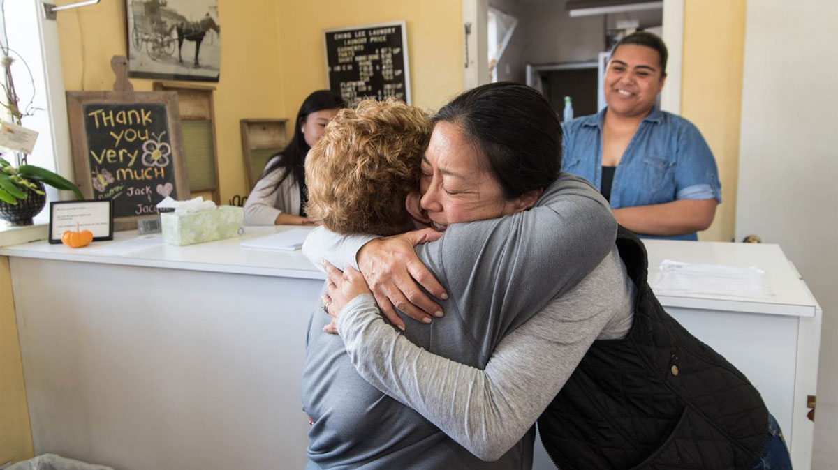 Jacque Yee, a fourth generation family member to operate Ching Lee Laundry, hugs a long-time customer on October 29, 2016.