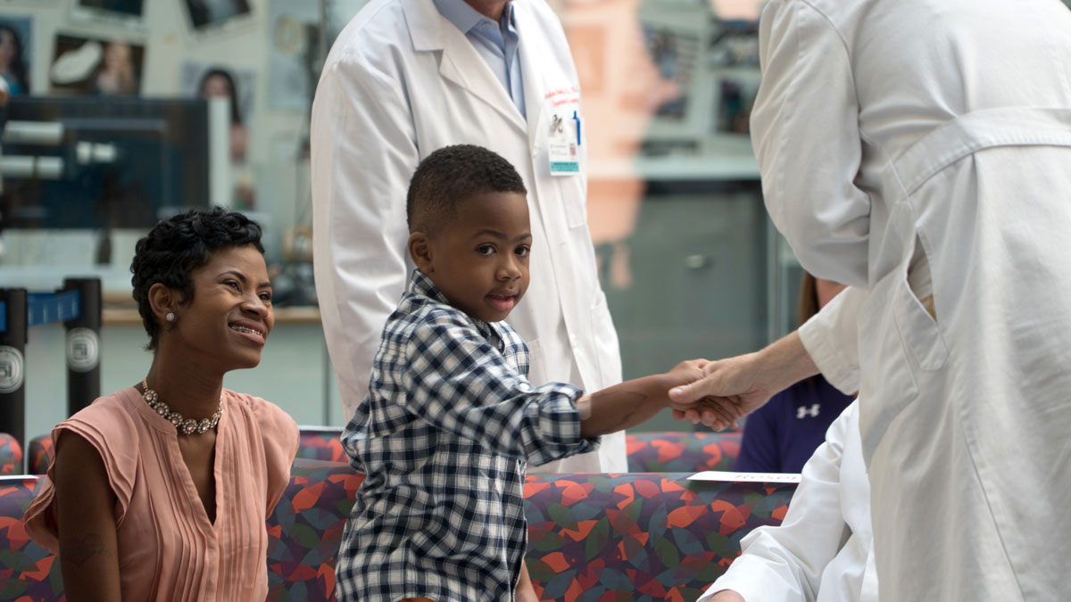 In this Aug. 23, 2016, photo, Zion Harvey, center, who received a double hand transplant in July 2015, shakes hands with a health care worker as his mother Pattie Ray, left, smiles during a news conference at The Children's Hospital of Philadelphia in Philadelphia.