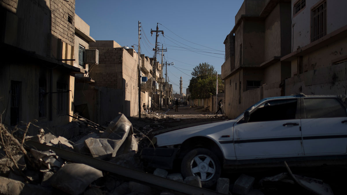 Iraqi special forces patrol on a street blocked by a destroyed car and debris as they advance towards Islamic State militant-held territory in Mosul, Iraq, Friday, Nov. 18, 2016.
