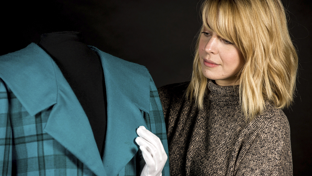 In this photo provided by Historic Royal Palaces, a conservator handles a blue tartan jacket designed by the Emanuels which was worn by Princess Diana during an official visit to Venice in 1985.