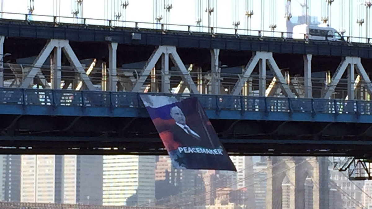 The banner of Vladimir Putin flapps off the side of the Manhattan Bridge on Thursday, Oct. 6. (@HeathRaymond / Twitter)