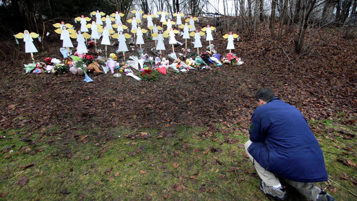 In this Dec. 18, 2012, file photo, Robert Soltis, of Newtown, Conn., pauses after making the sign of the cross at a memorial to Sandy Hook Elementary School shooting victims in Newtown.
