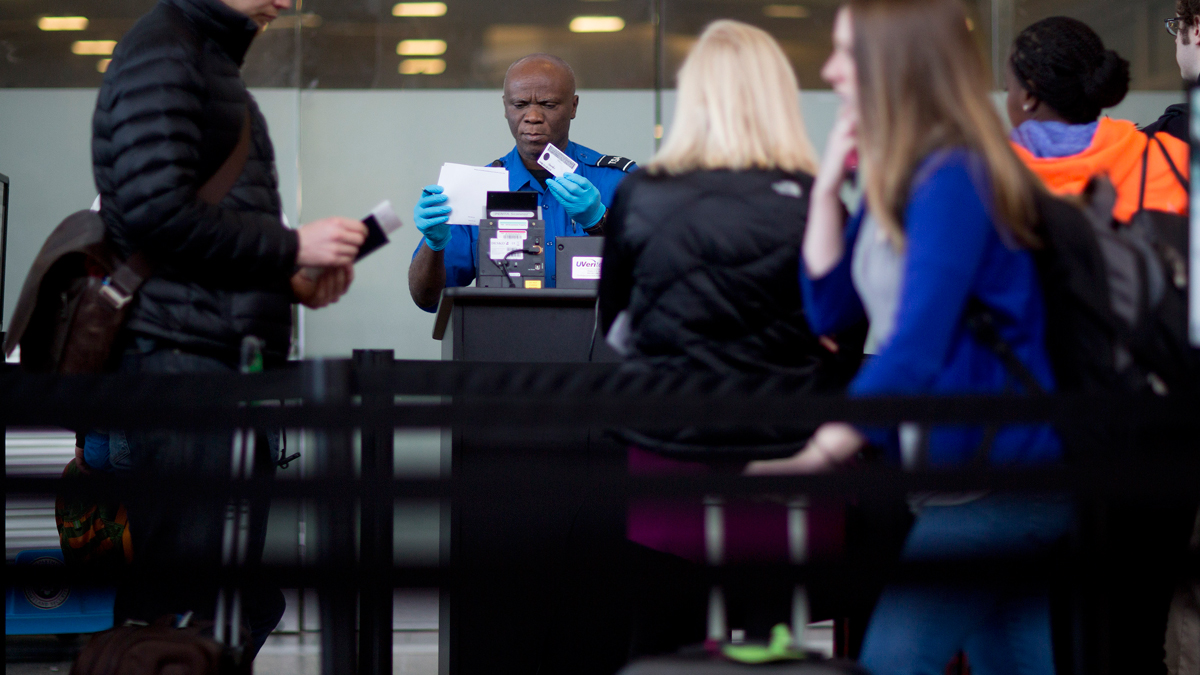 File - A Transportation Security Administration (TSA) officer checks a passenger's identification and boarding pass at a security checkpoint at Ronald Reagan National Airport (DCA) in Washington, D.C., U.S., on Wednesday, Feb. 25, 2015.