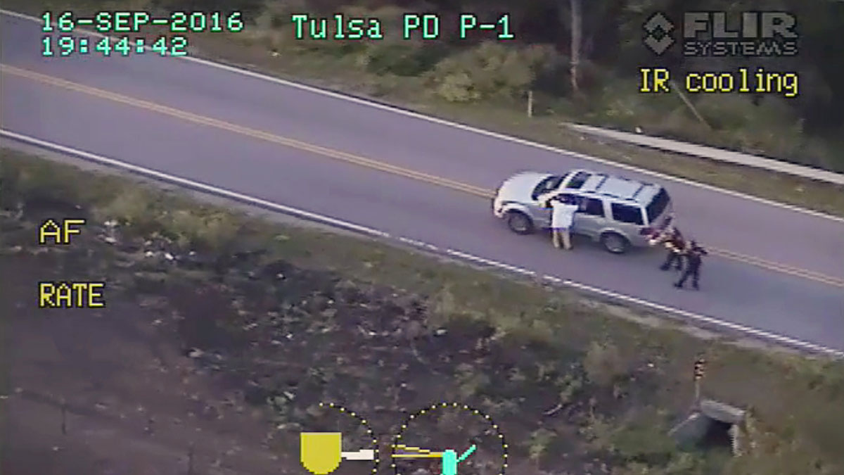 In this photo made from a Sept. 16, 2016 police video, Terence Crutcher, left, with his arms up is pursued by police officers as he walks next to his stalled SUV moments before he was shot and killed by one of the officers in Tulsa, Oklahoma.