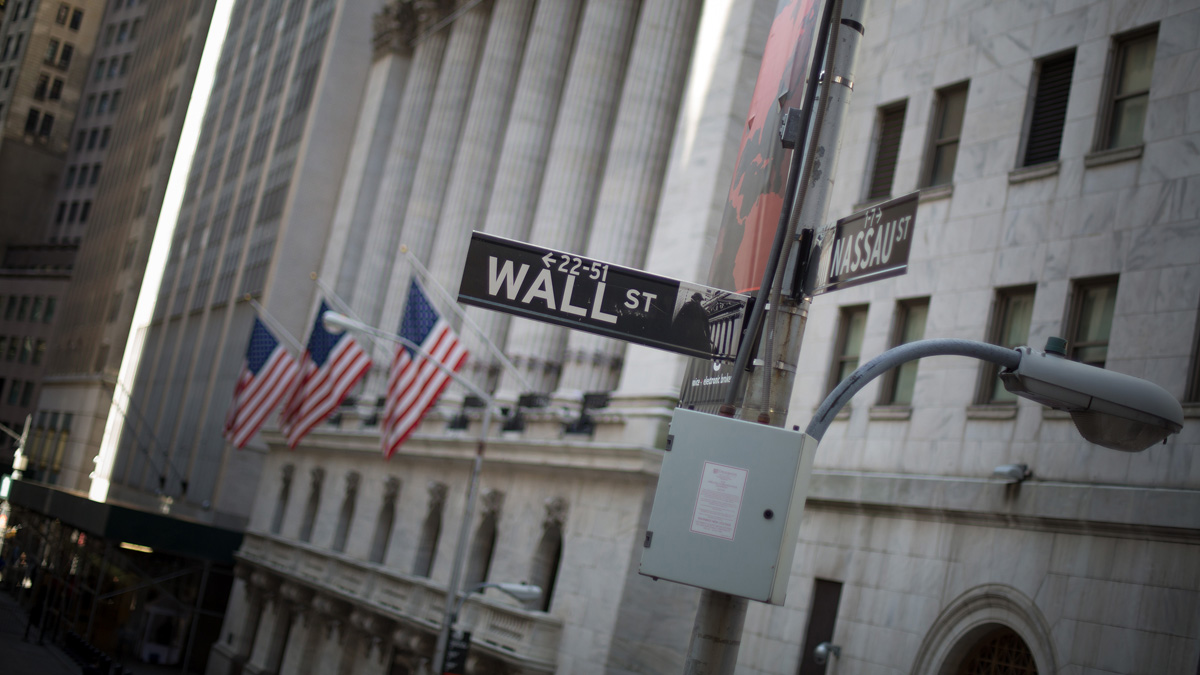 A Wall Street sign is displayed in front of the New York Stock Exchange.